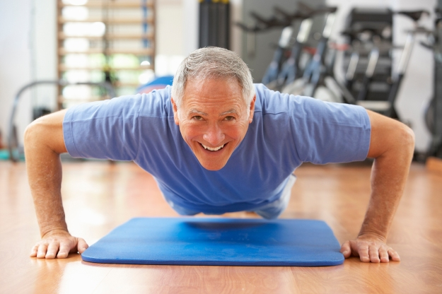 Senior Man Doing Press Ups In Gym